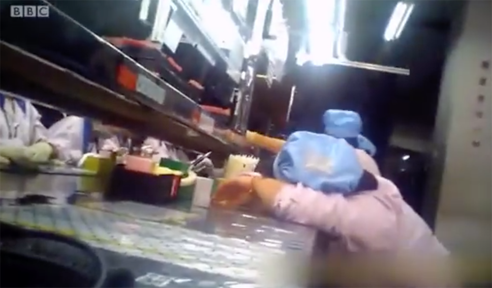 A screengrab from the documentary showing workers sleeping on the production-line