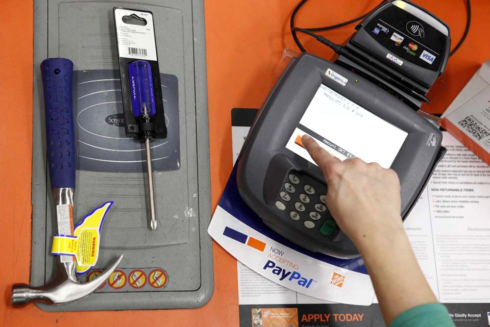 A public relations representative demonstrates how a PayPal customer can pay for goods using their mobile phone number at a cashier station at a Home Depot store in Daly City