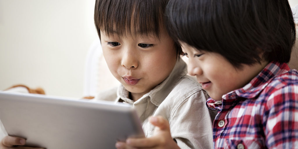 Two boys playing with a digital tablet.