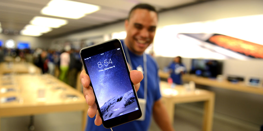 IMAGE DISTRIBUTED FOR APPLE - An Apple Store employee shows off a new iPhone at the iPhone 6 launch at the Eaton Centre Apple Store on Friday, September 19, 2014, in Toronto. (Photo by Ryan Emberley/Invision for Apple/AP Images)