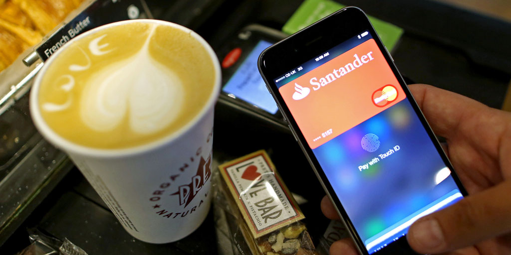 A customer uses an Apple Inc. iPhone to pay via the Apple Pay system, from their Santander account, at the check-out till inside a Pret A Manger Ltd store in this arranged photograph in London, U.K., on Tuesday, July 14, 2015. Apple Inc. is making the U.K. the first market outside the U.S. for its digital-wallet system as the company fights for a place in the electronic-payments industry. Photographer: Chris Ratcliffe/Bloomberg via Getty Images