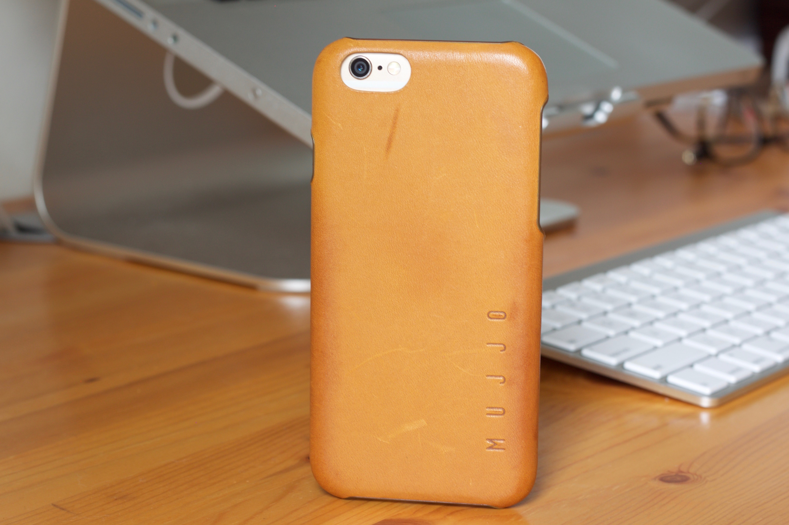 Mujjo Leather Case in Tan with an iPhone 6 propped vertically in front of a keyboard