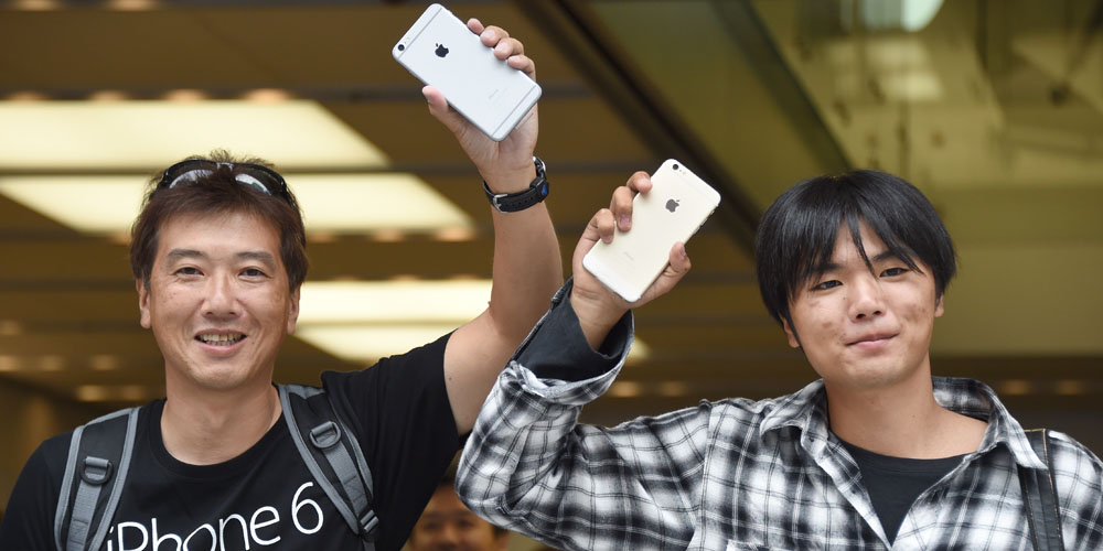 Customers display their iPhone 6 handsets at an Apple store in the Ginza shopping district in Tokyo on September 19, 2014. Apple's new smartphone iPhone 6 was released in Japan on September 19. AFP PHOTO/Toru YAMANAKA (Photo credit should read TORU YAMANAKA/AFP/Getty Images)
