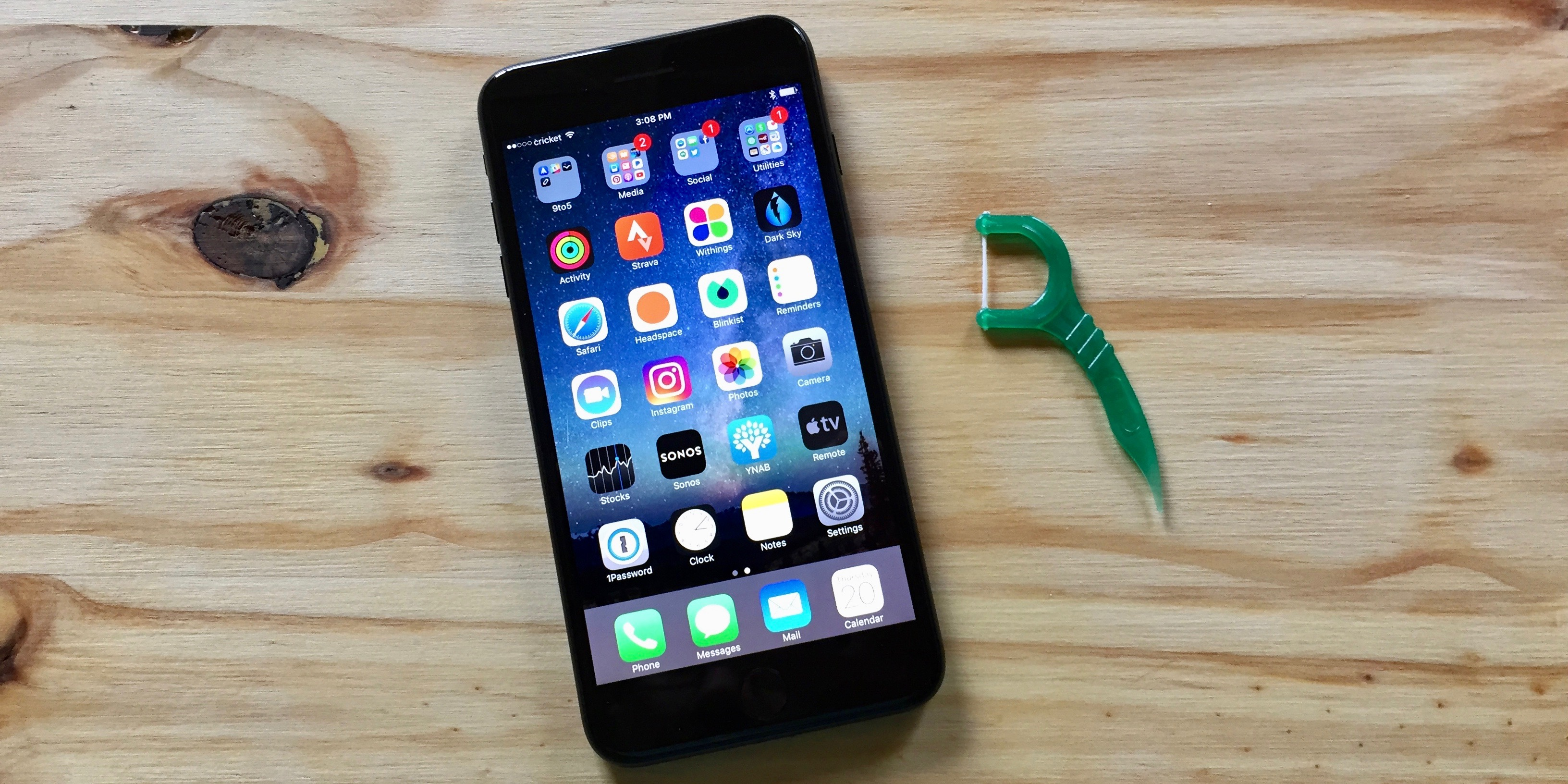 Image of iPhone 7 Plus and plastic dental pick that can be used to clean out a Lightning port