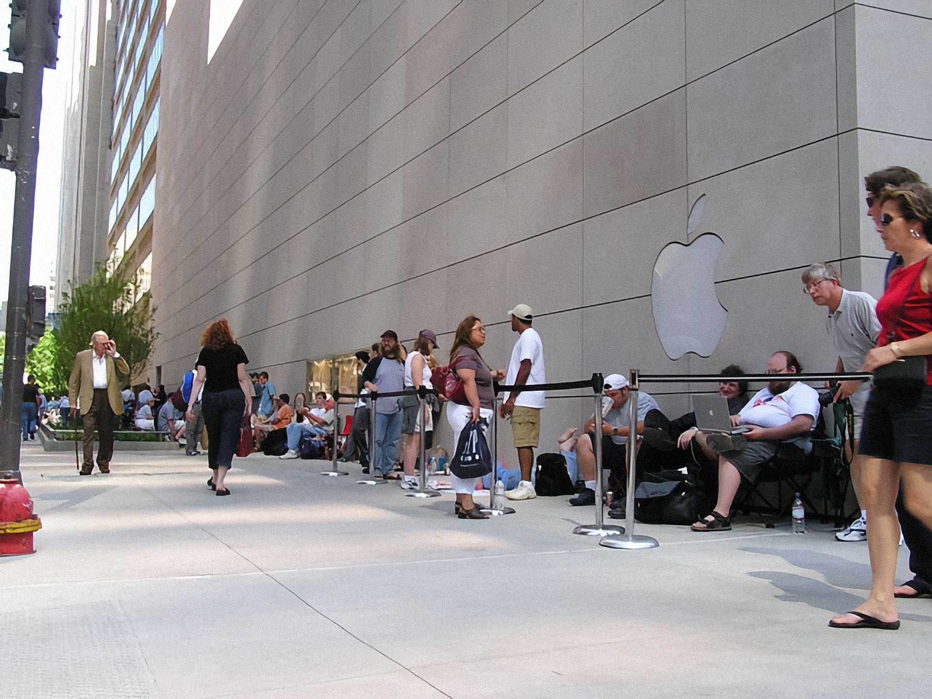 Customers wait outside behind stanchions to enter Apple North Michigan Avenue.