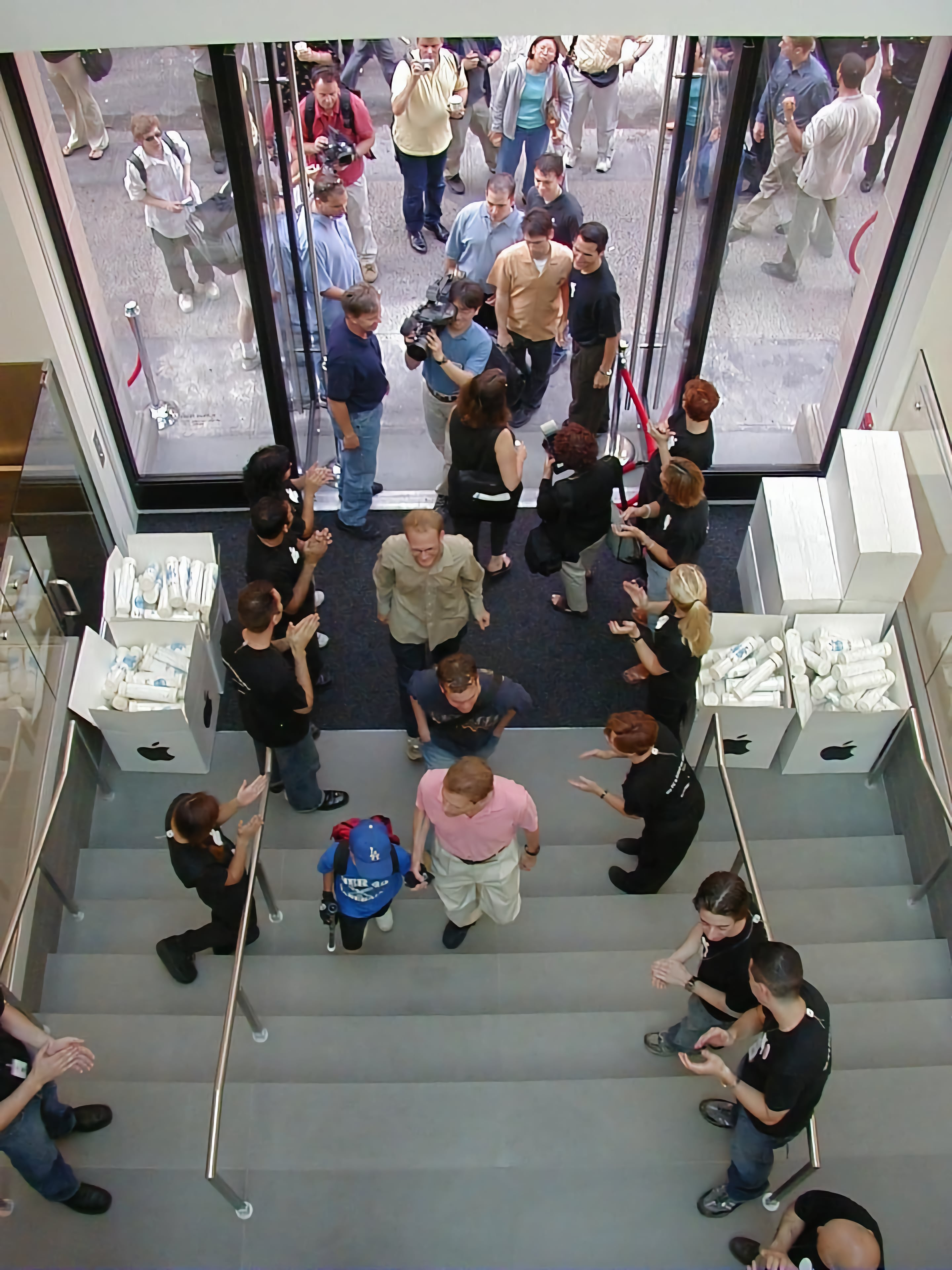Customers walk up steps to enter Apple SoHo on grand opening day.